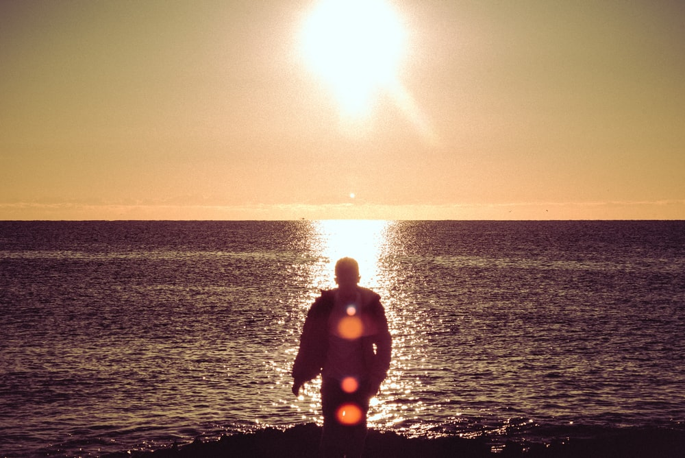 man in black wet suit standing on sea shore during sunset