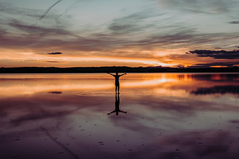 silhouette of man standing on body of water during sunset