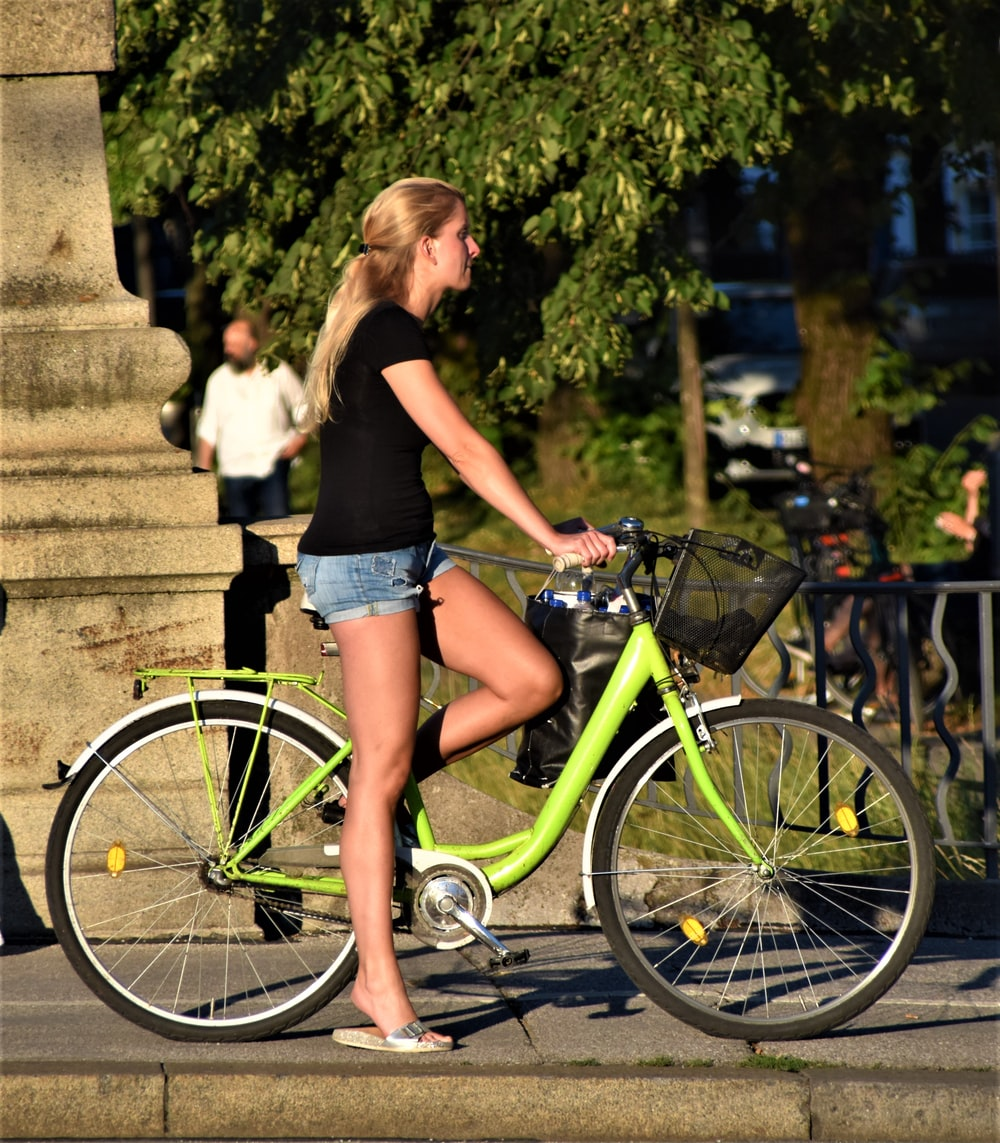 Pretty lady rides with green comfort bicycle