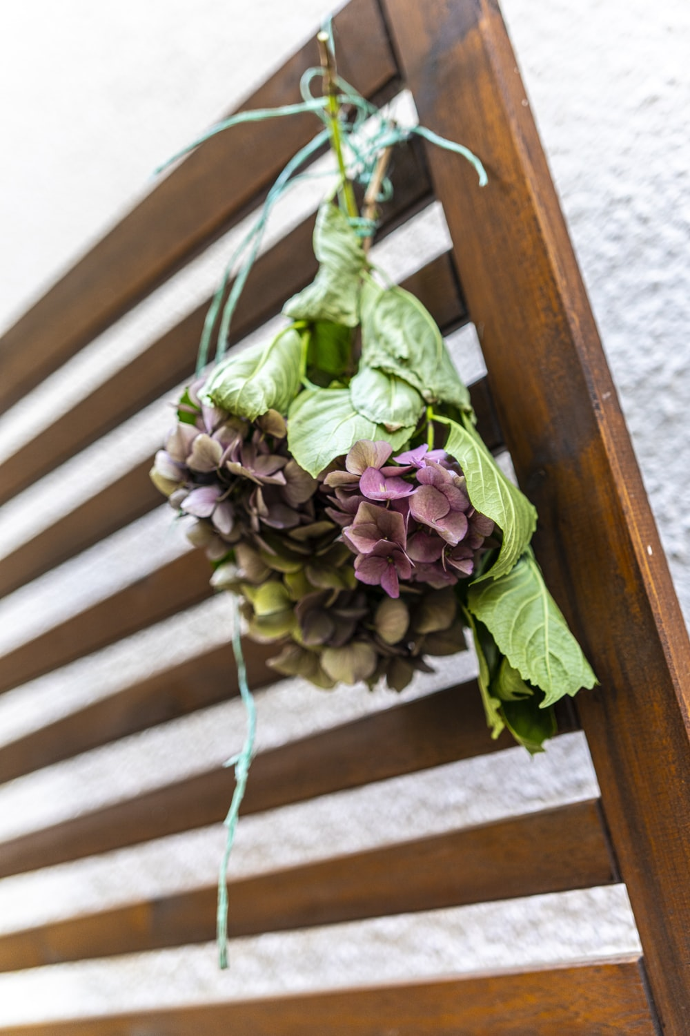 green and purple flower bouquet on brown wooden staircase
