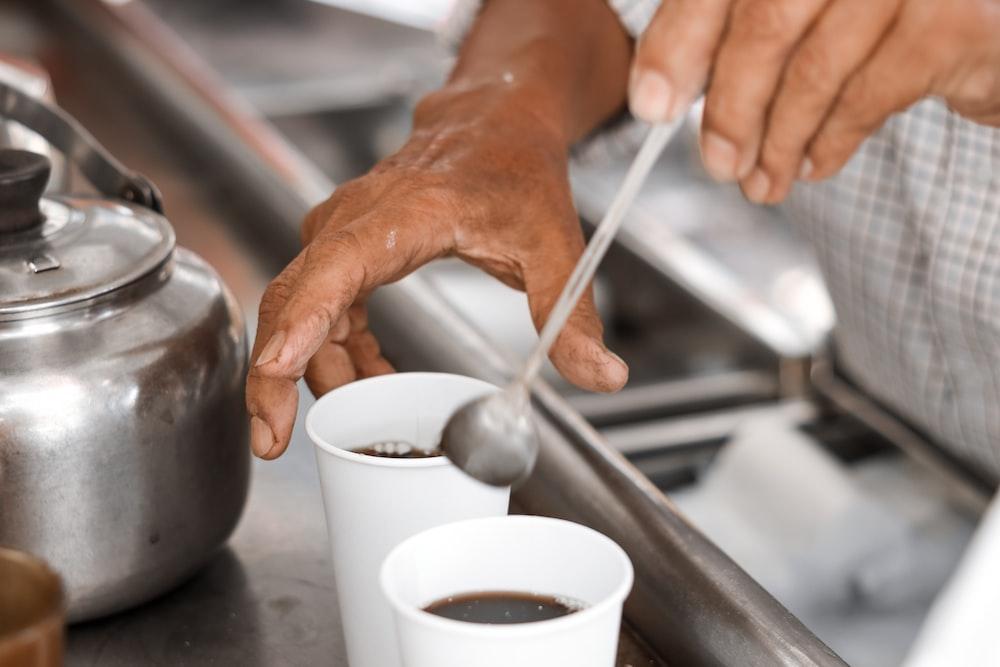 person pouring water on white ceramic mug