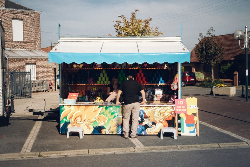 people sitting on white and blue food stall during daytime