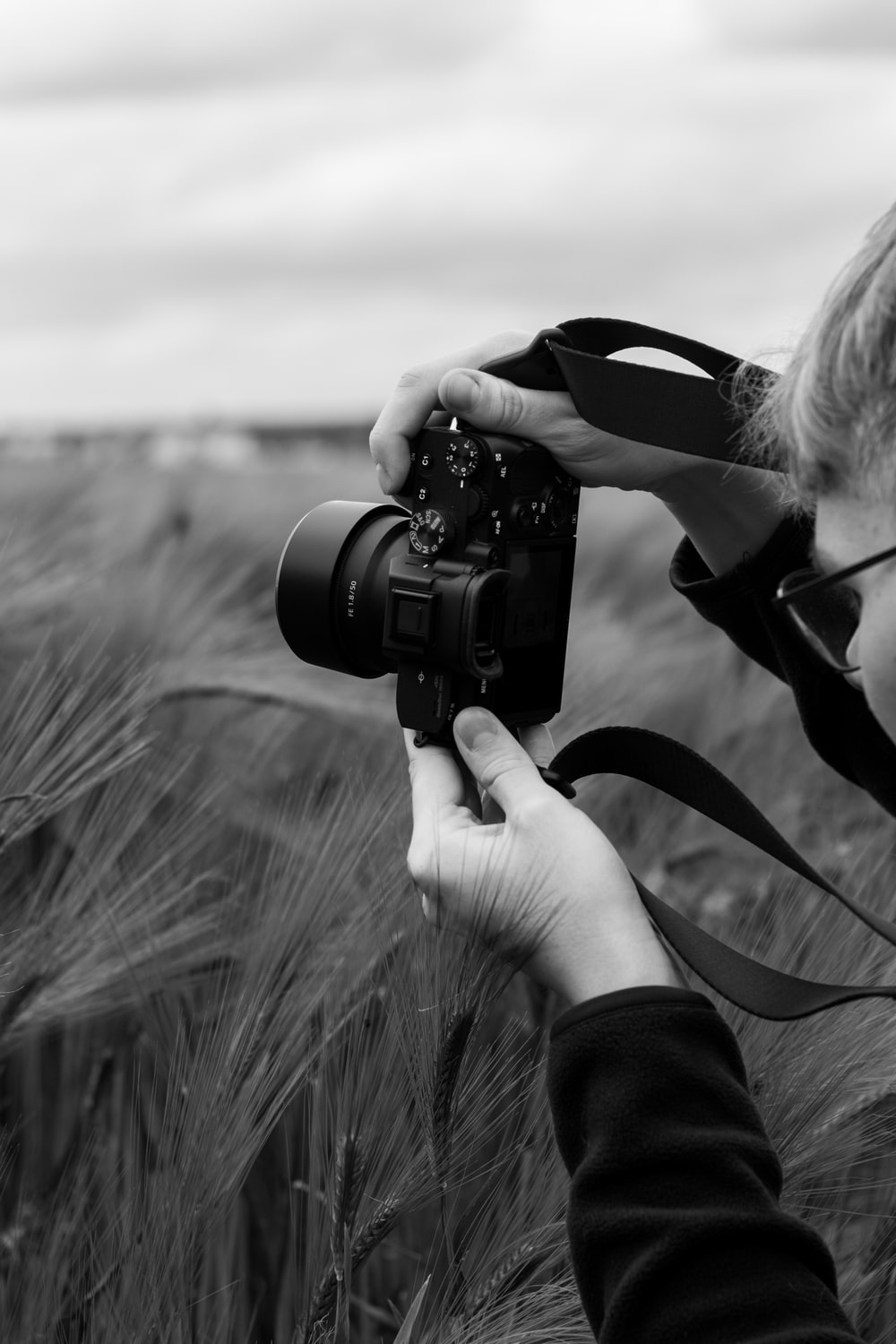 grayscale photo of man holding dslr camera
