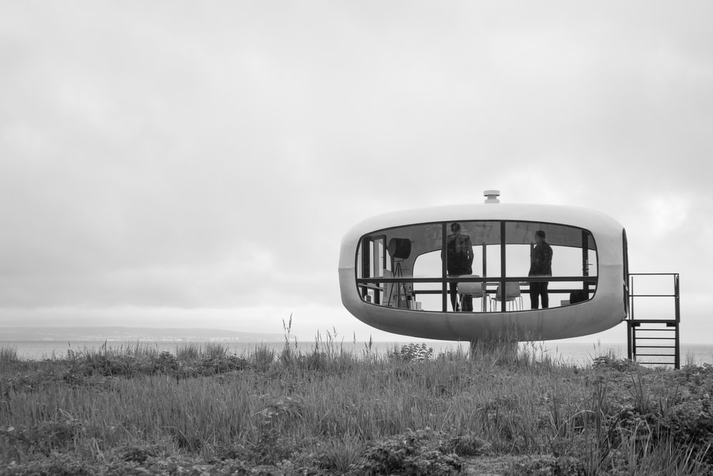 grayscale photo of a building in the middle of a field