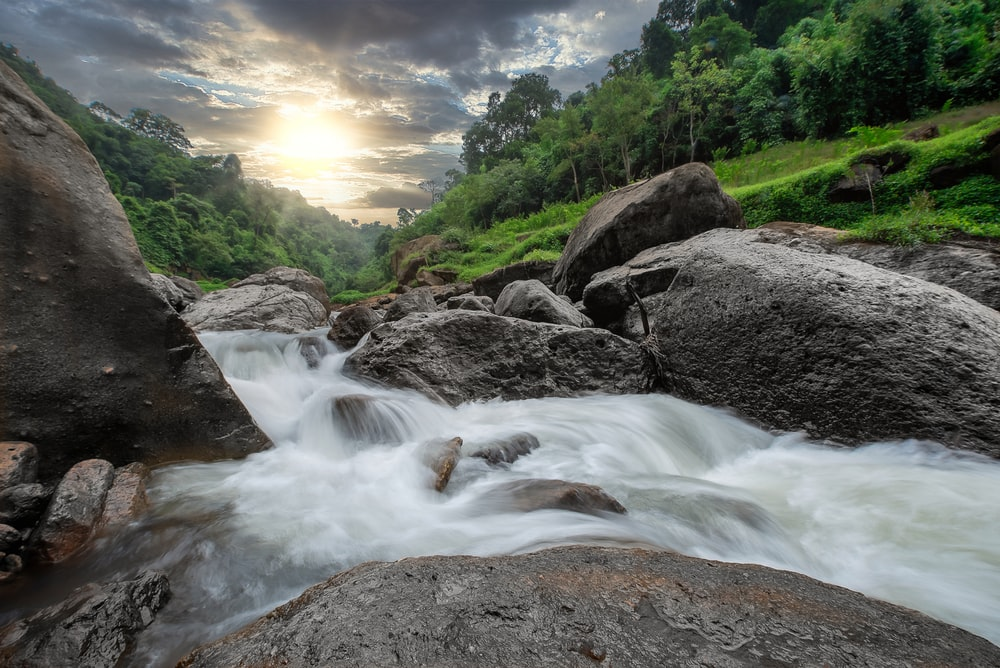 time lapse photography of river between green trees during daytime