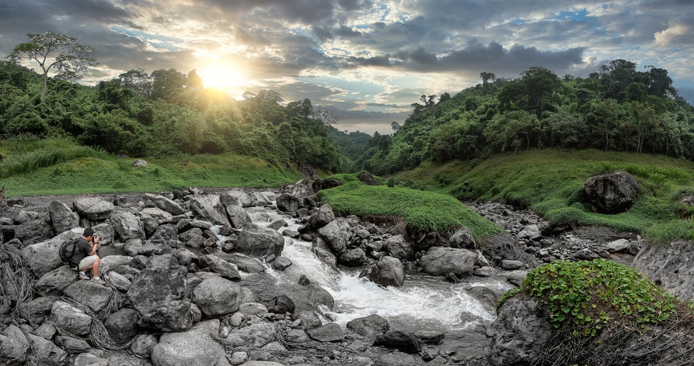 rocky river with rocks and green grass under blue sky and white clouds during daytime