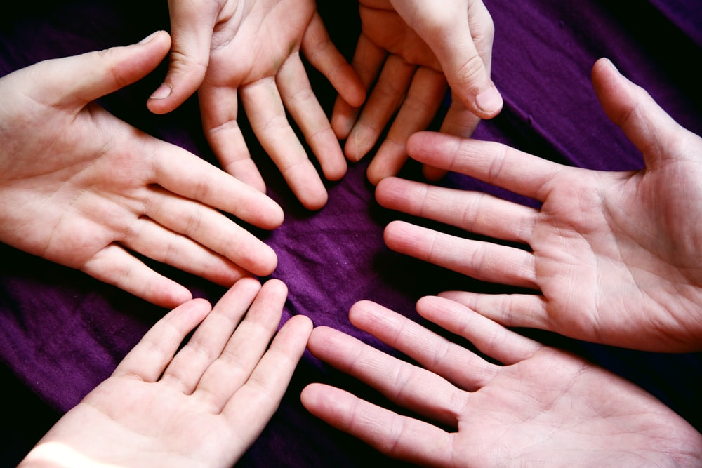 persons left hand on purple textile