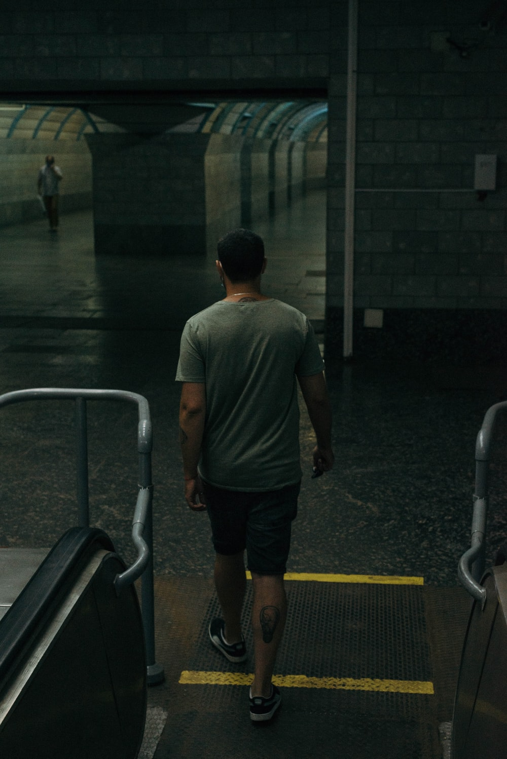 man in gray t-shirt and black shorts walking on hallway
