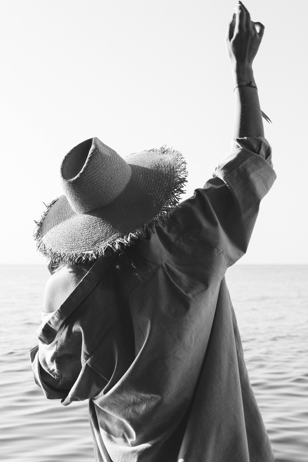 grayscale photo of woman wearing sun hat and sunglasses