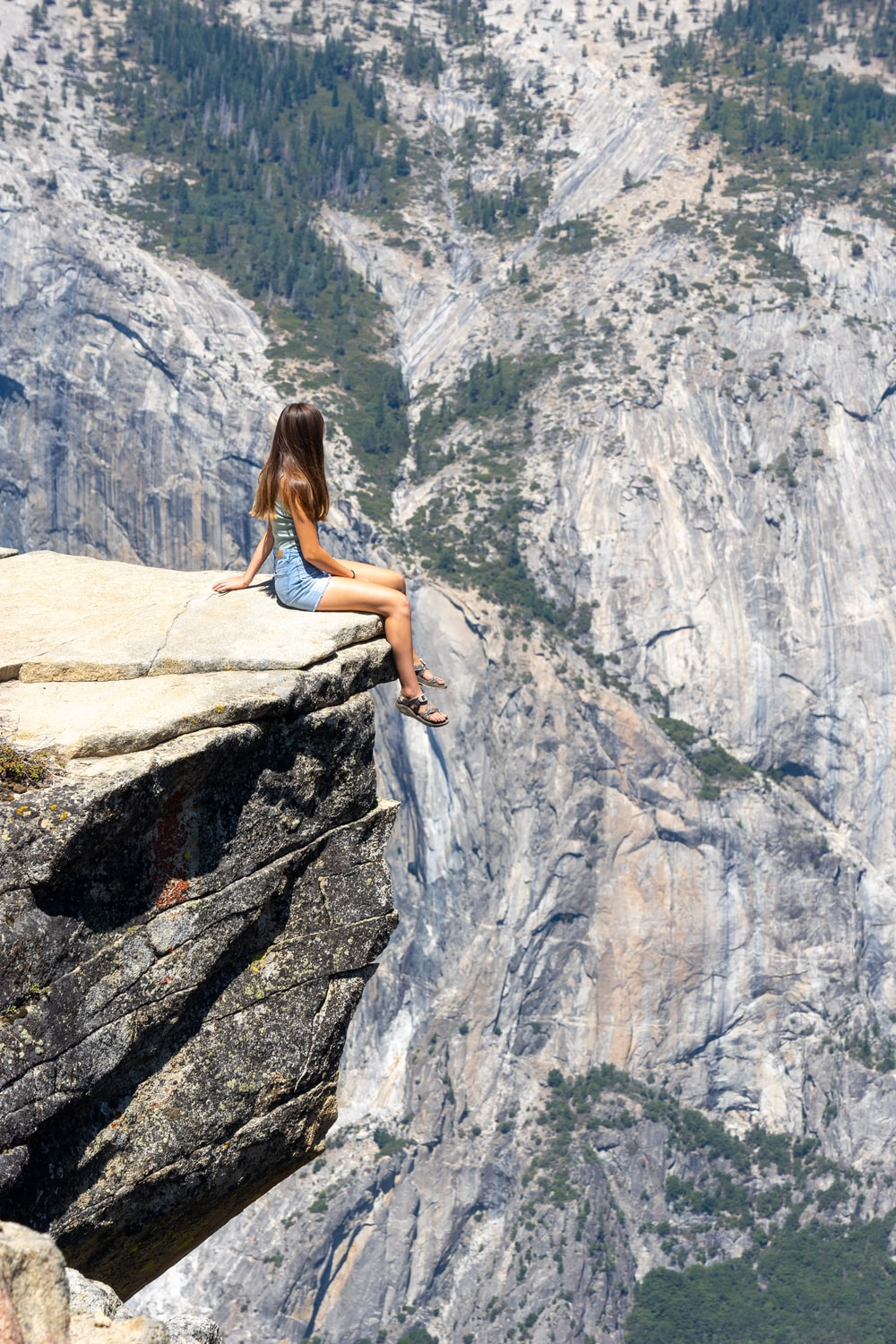 woman in white tank top and blue denim shorts sitting on rock formation during daytime