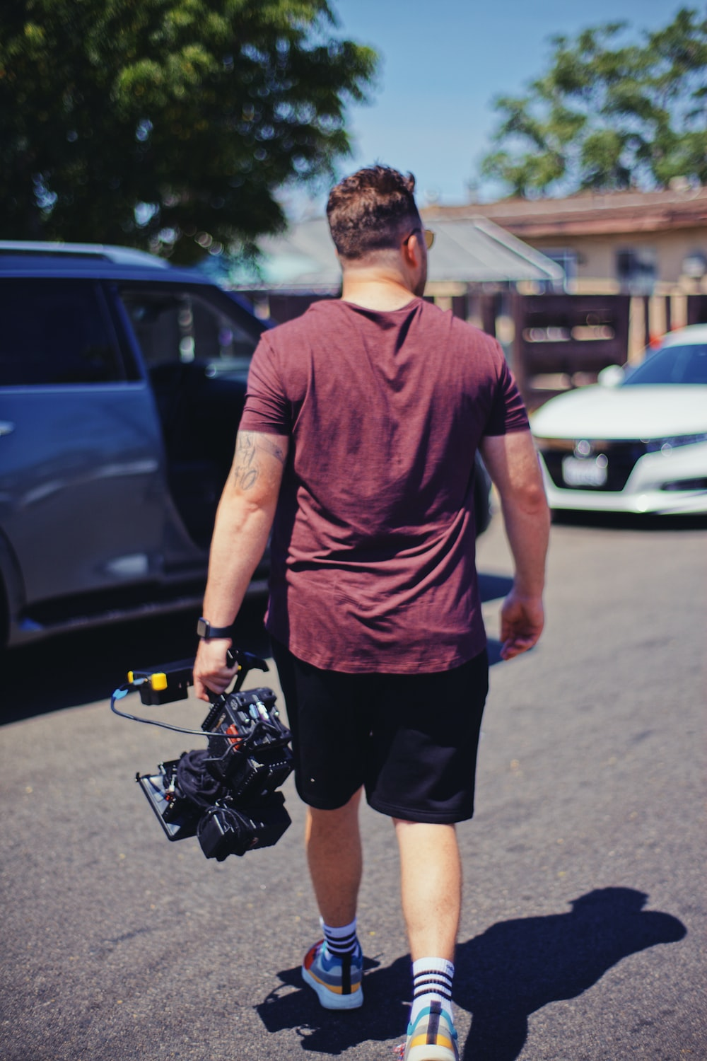 man in purple crew neck t-shirt and black shorts standing on gray concrete pavement during