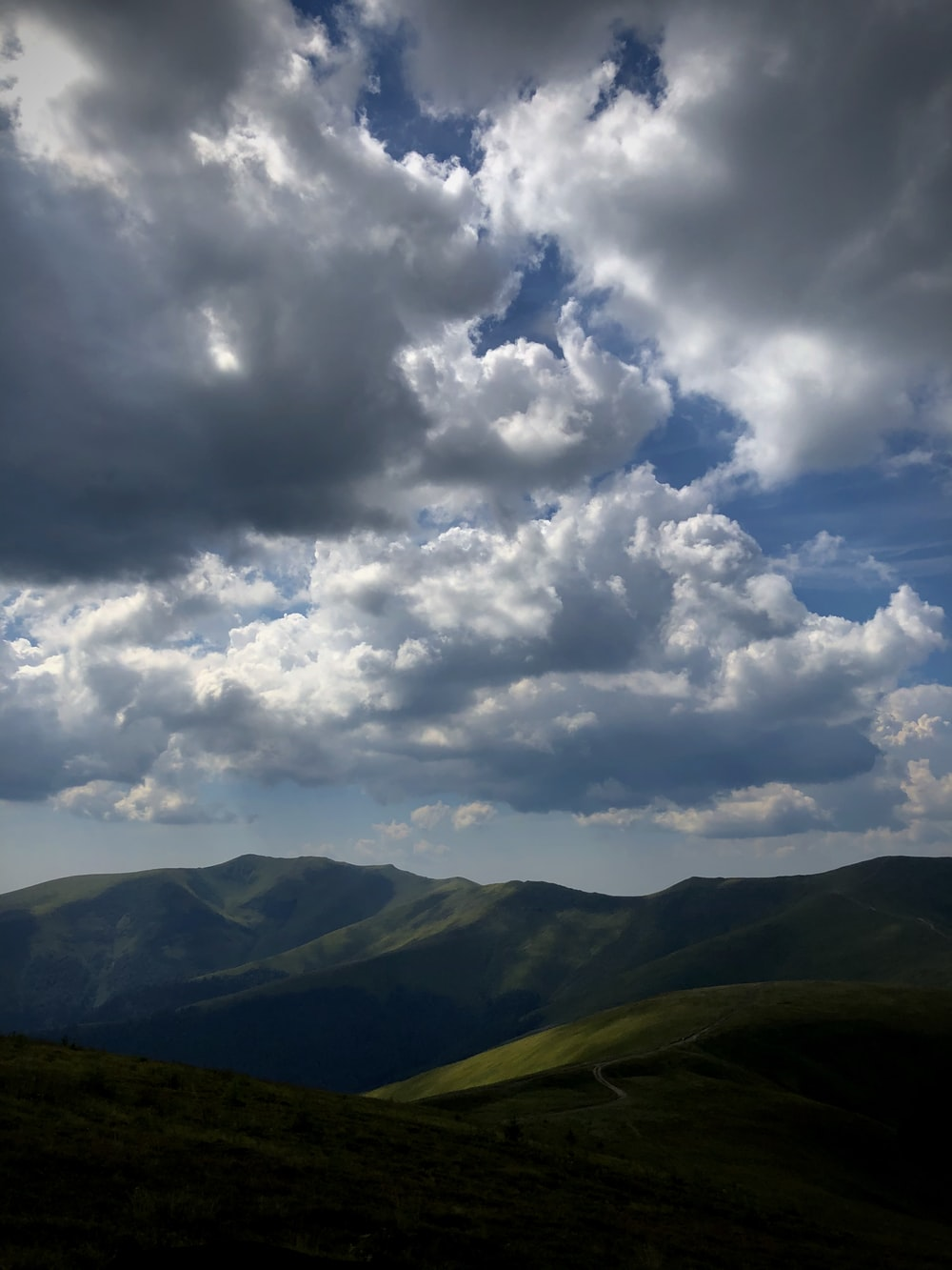 green mountains under white clouds and blue sky during daytime