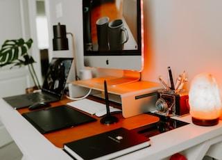 silver imac on black wooden desk