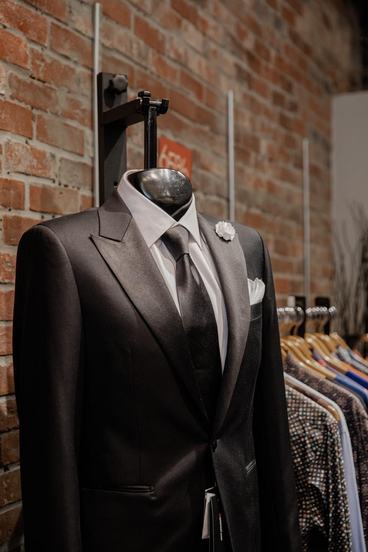 black suit jacket near brown brick wall