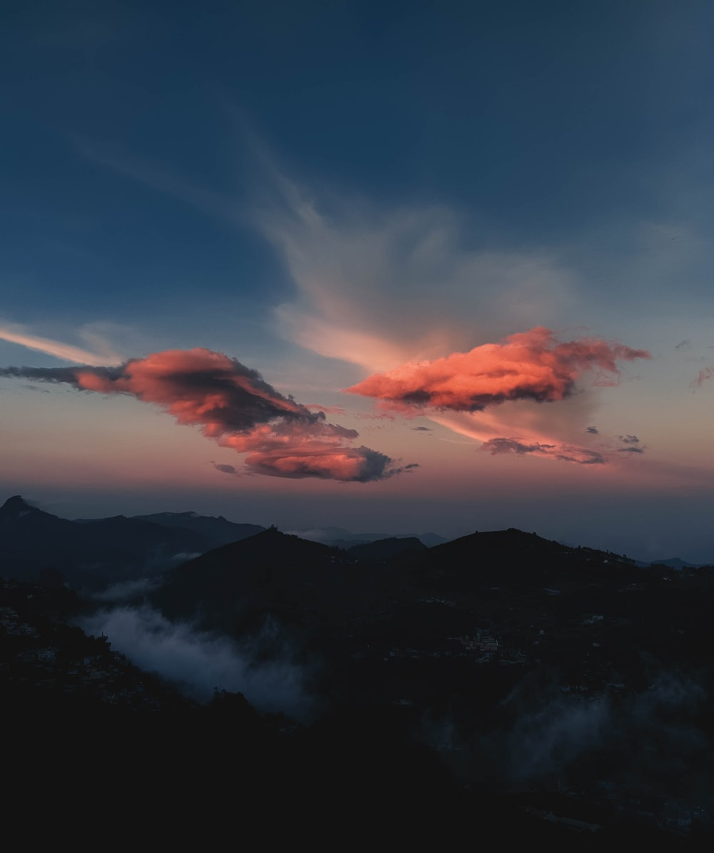 silhouette of mountain under cloudy sky during sunset