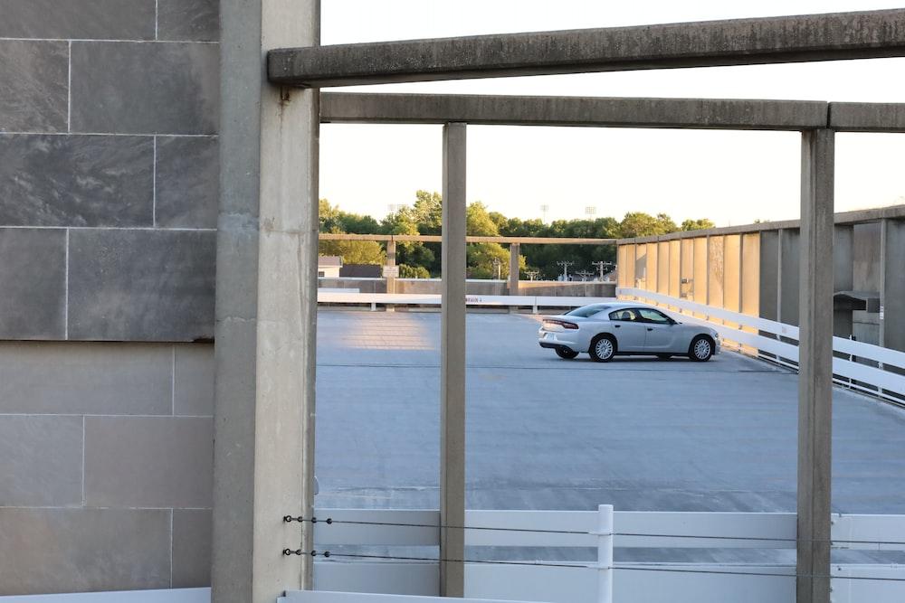 black sedan parked beside white metal railings