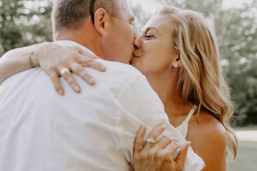 man in white shirt kissing woman in white spaghetti strap top