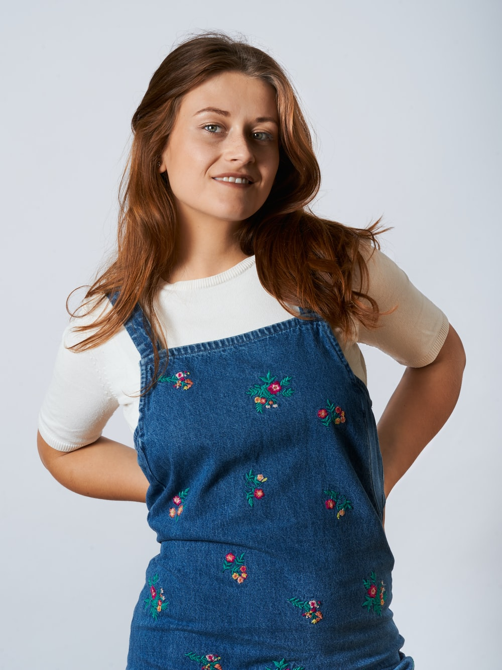girl in white long sleeve shirt and blue denim dungaree
