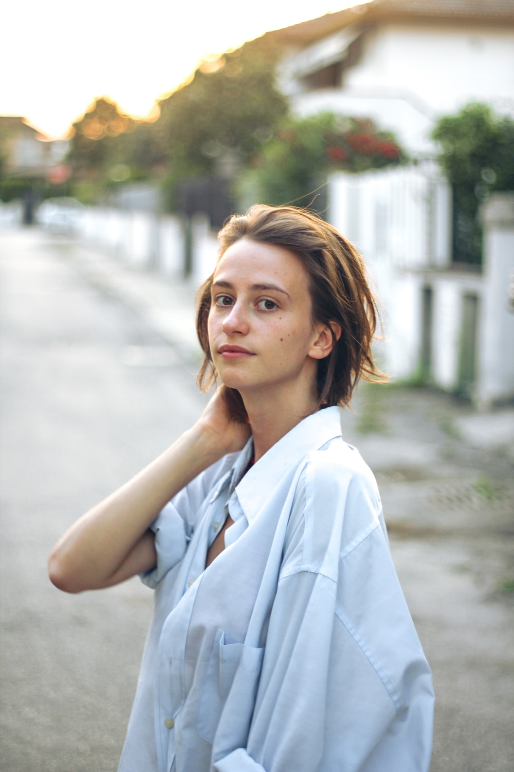woman in white button up shirt standing on road during daytime