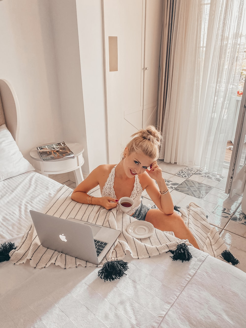 woman in white tank top sitting on bed using macbook