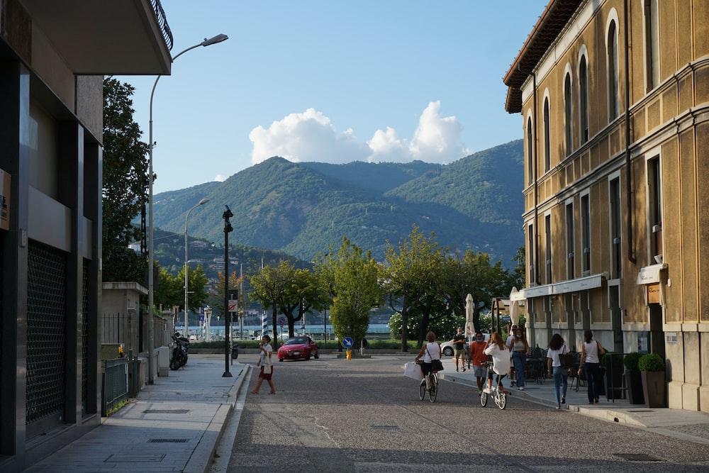 people walking on sidewalk near mountain during daytime