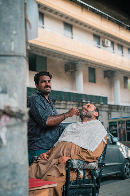 man in gray dress shirt sitting on mans lap