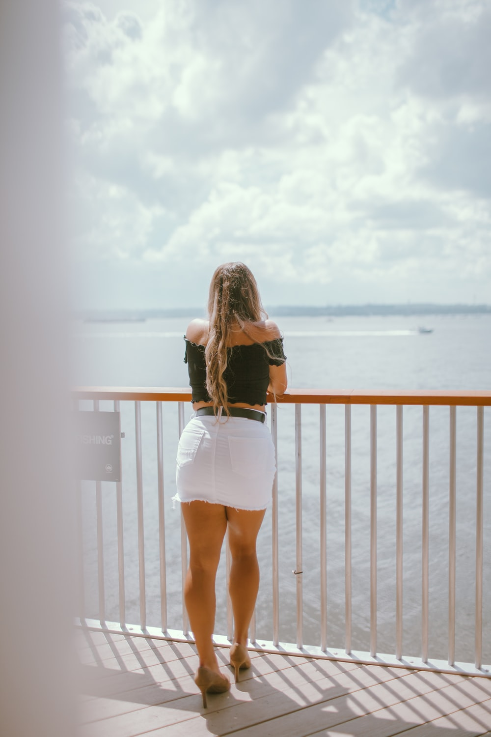 woman in white mini dress standing on brown wooden dock during daytime