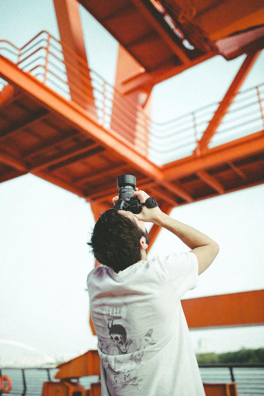 man in white t-shirt holding black dslr camera