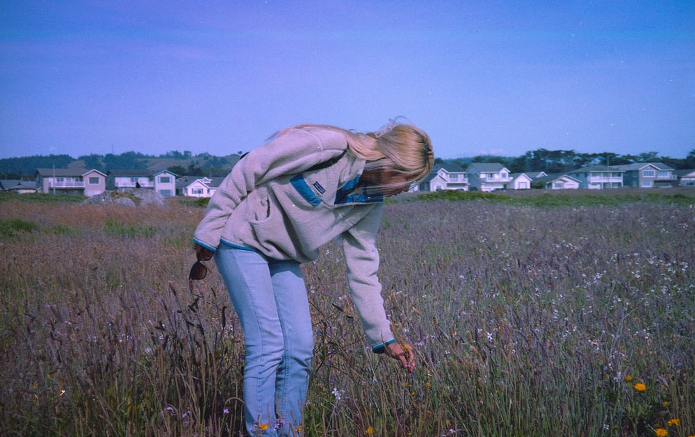 woman in green hoodie and blue denim jeans standing on green grass field during daytime