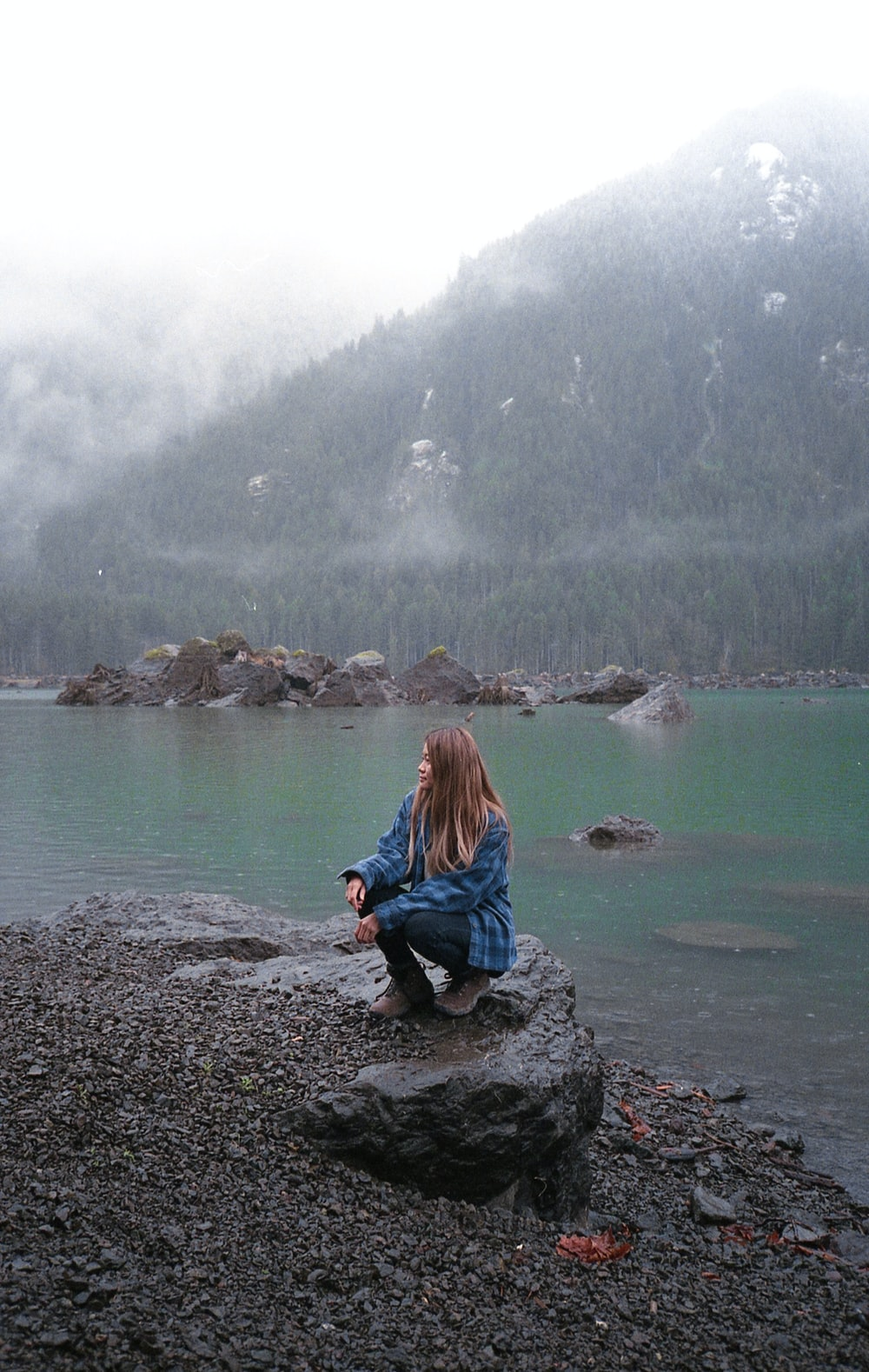 woman in blue jacket sitting on rock by the lake during daytime