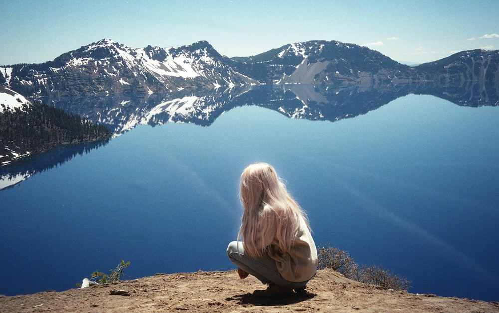 woman in white shirt sitting on brown rock looking at the snow covered mountain during daytime