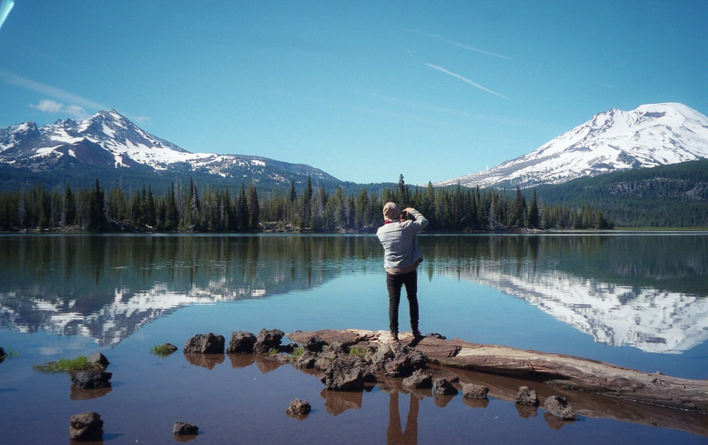 woman in white long sleeve shirt and blue denim jeans standing on brown log near lake