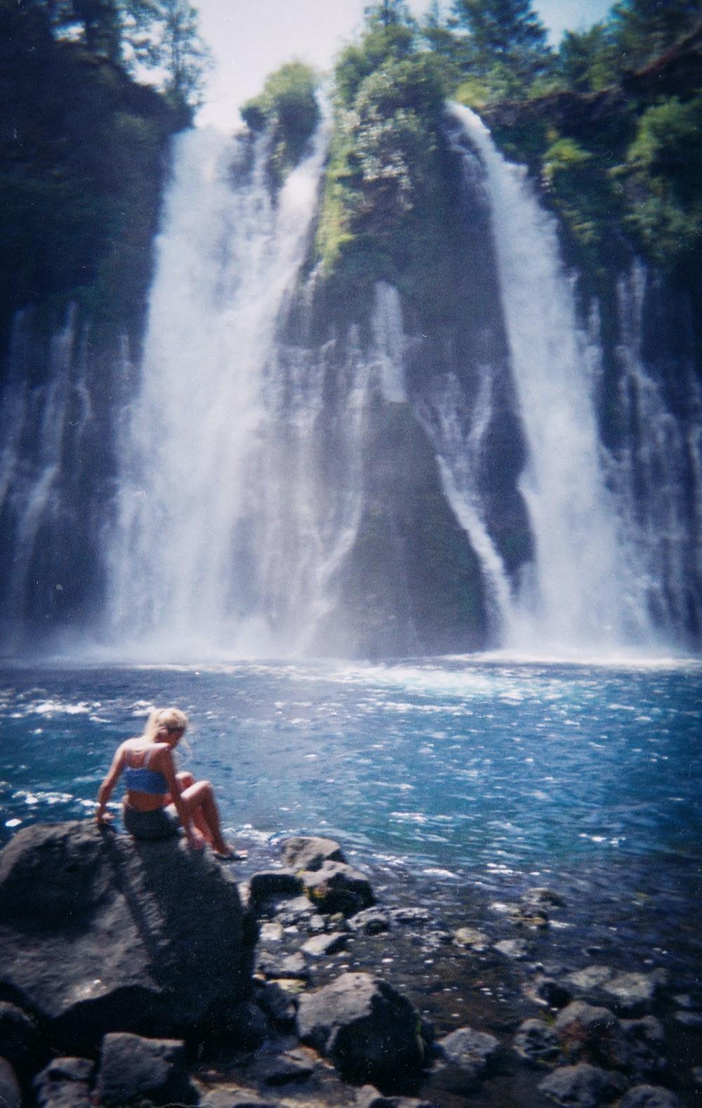woman in black bikini sitting on rock near waterfalls during daytime