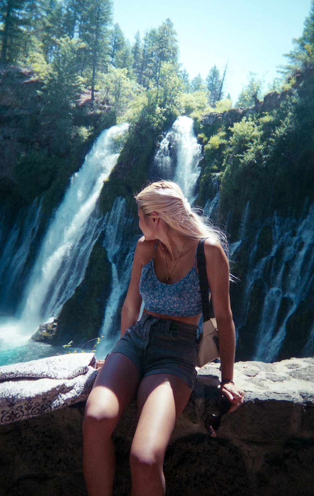 woman in blue tank top and blue denim shorts sitting on rock near waterfalls during daytime