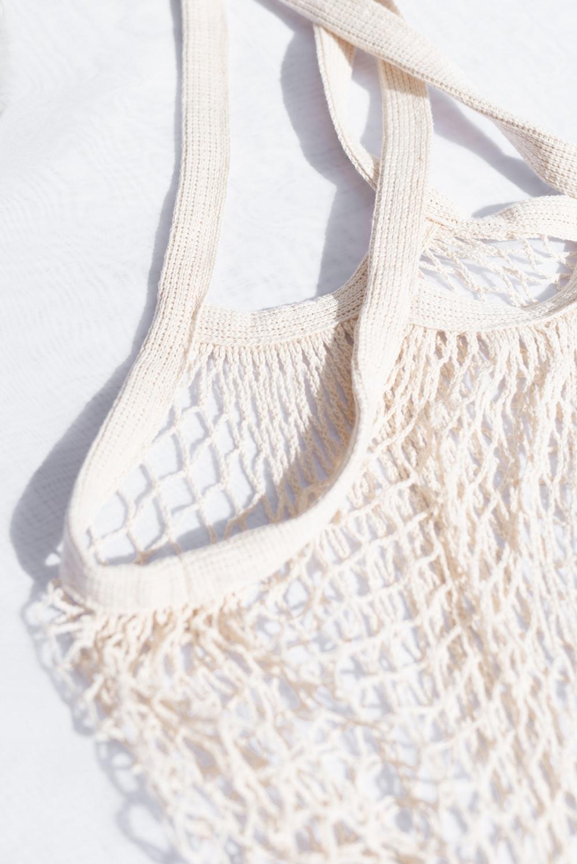 white knit bag on white textile