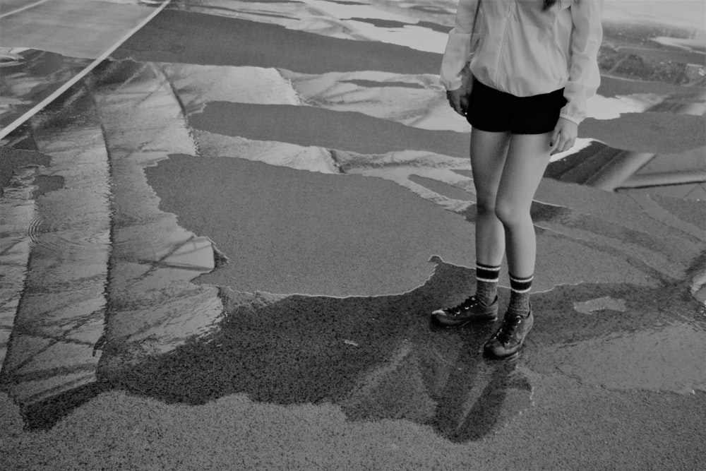 woman in white long sleeve shirt and black skirt walking on gray concrete road