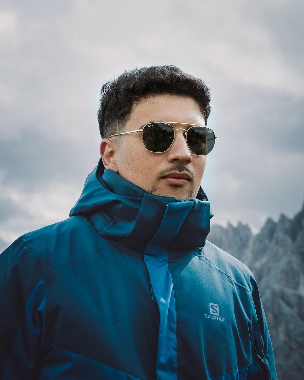 man in blue hoodie wearing black sunglasses