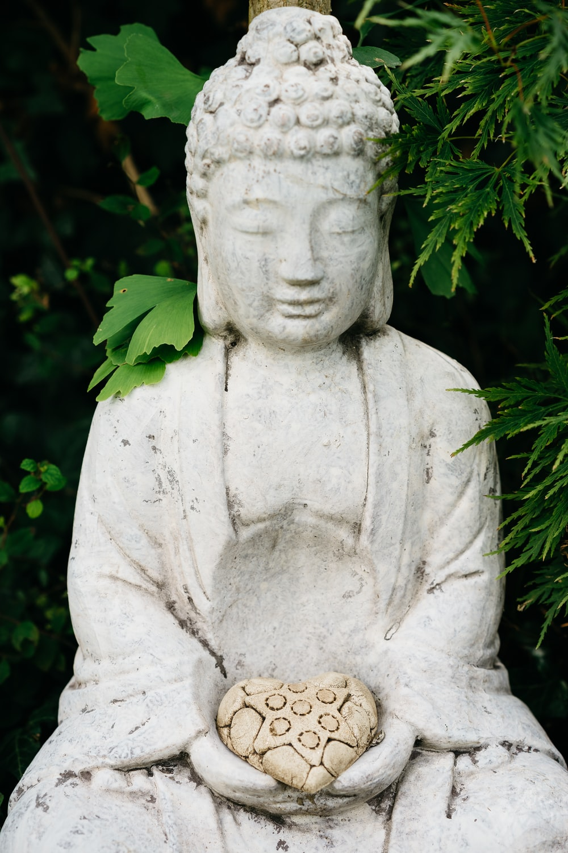 gray concrete statue near green plants