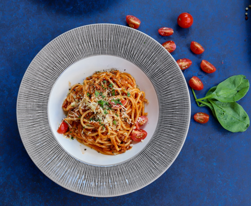 pasta with red sauce on white ceramic round plate