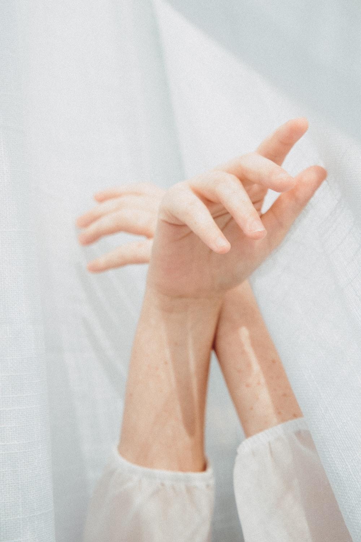 persons feet on white textile