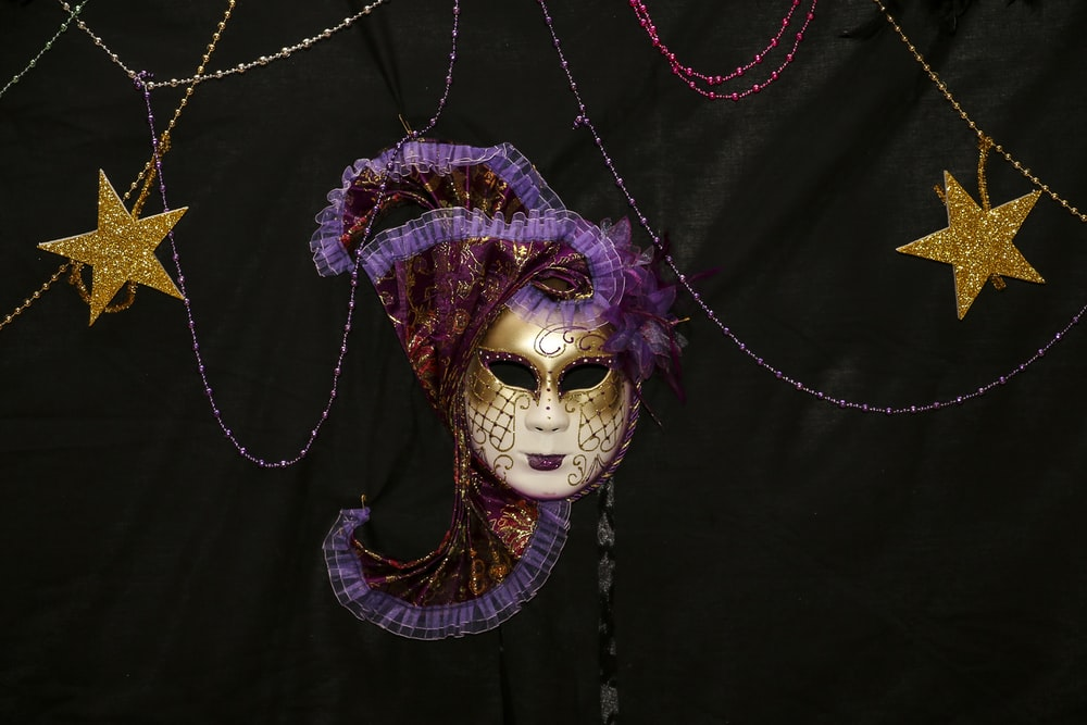 white and purple mask on black textile