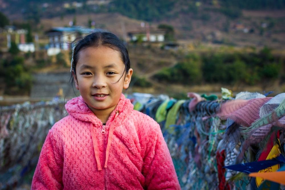 girl in pink zip up hoodie smiling