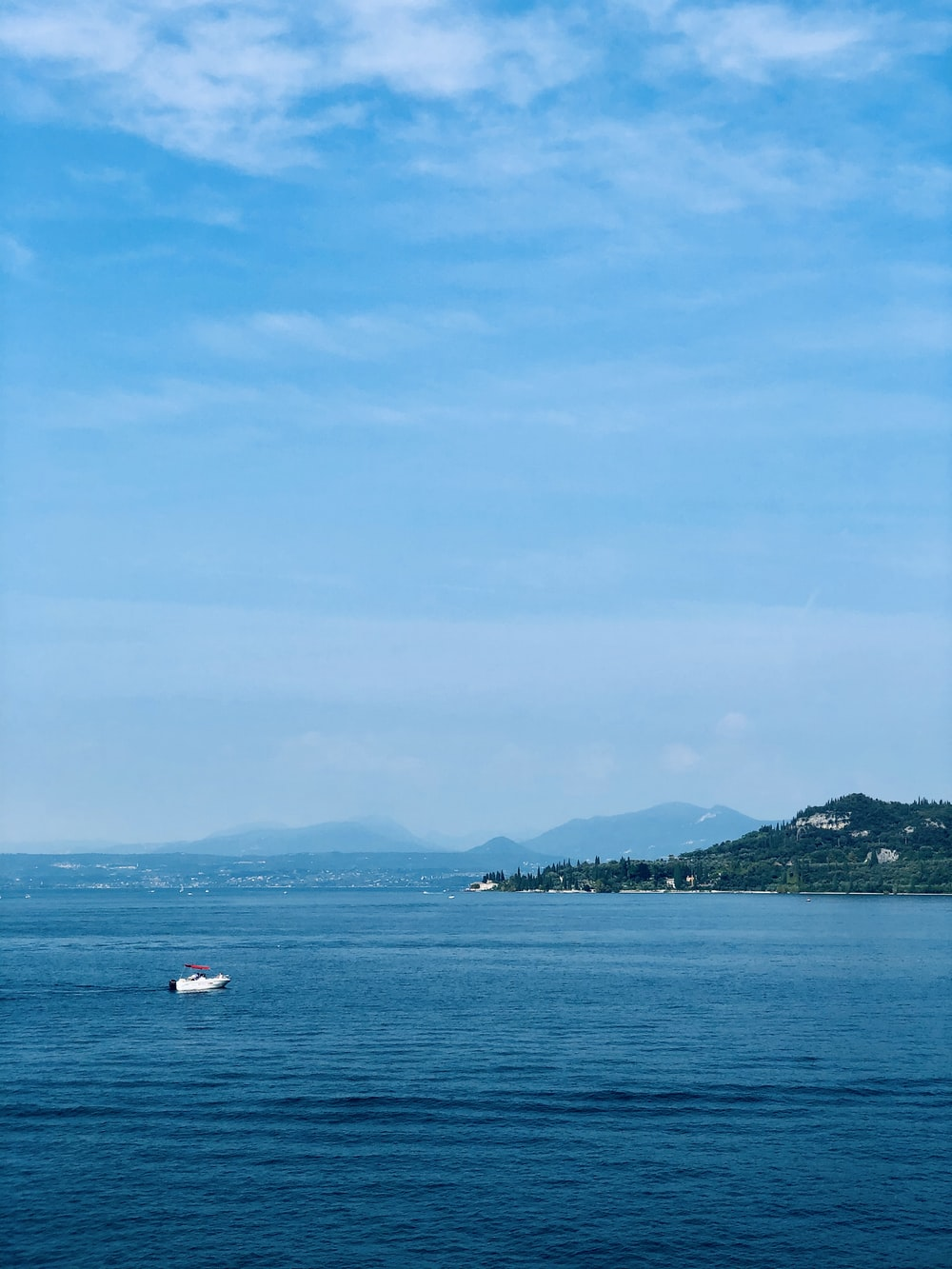white boat on sea near green mountain under blue sky during daytime