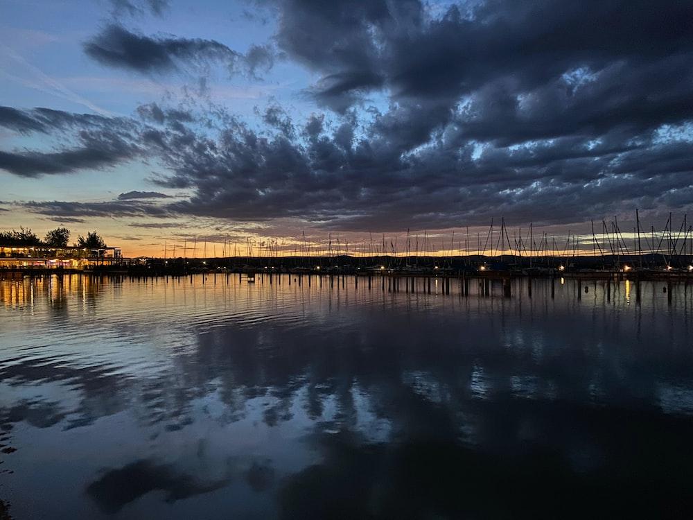 brown wooden dock on body of water under dark clouds