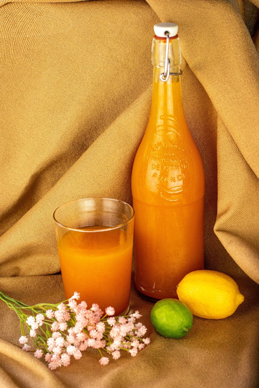 orange juice in clear glass bottle