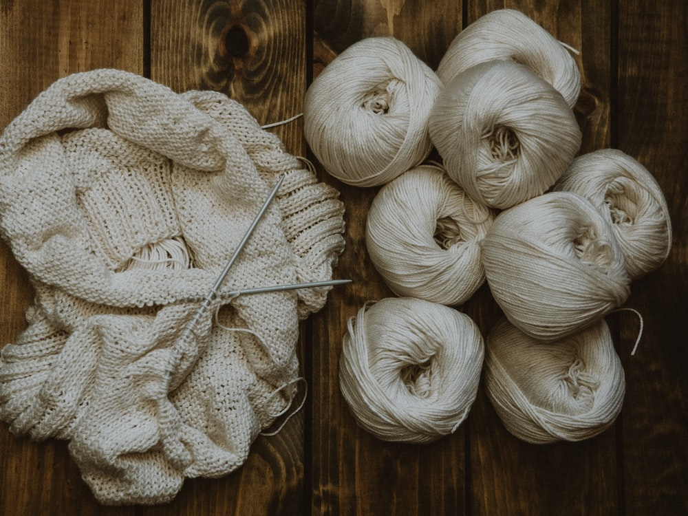 white yarn on brown wooden table