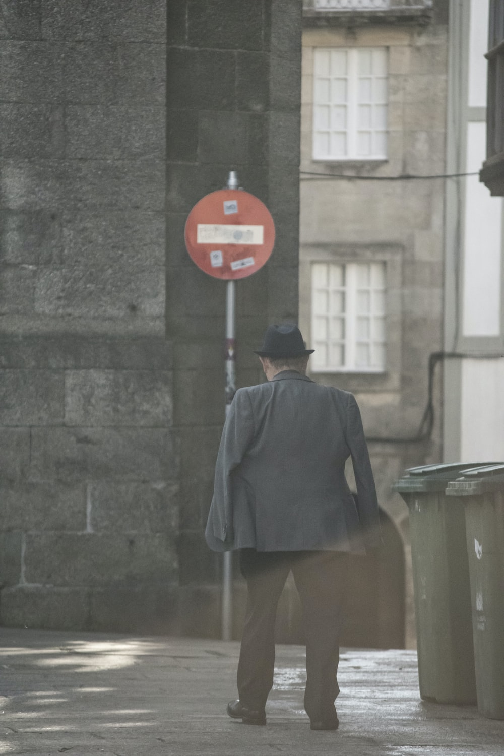 man in black coat standing near red stop sign