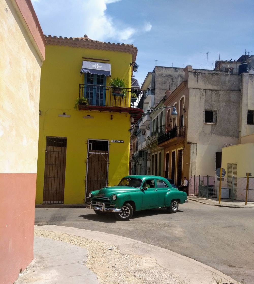 green sedan parked beside yellow concrete building during daytime