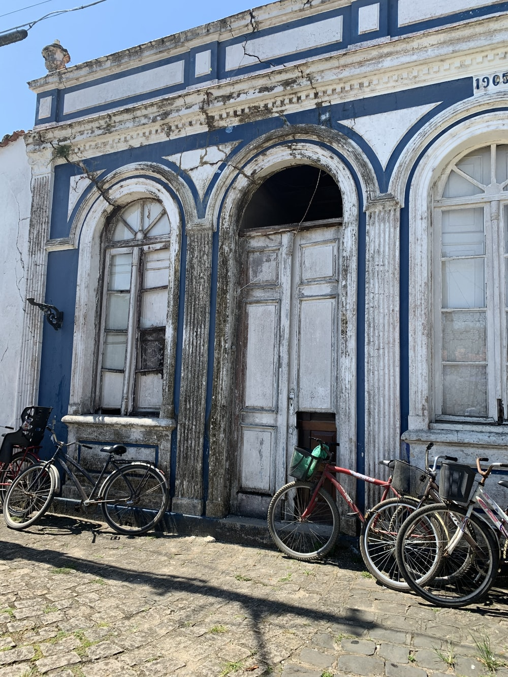 bicycles parked in front of blue concrete building