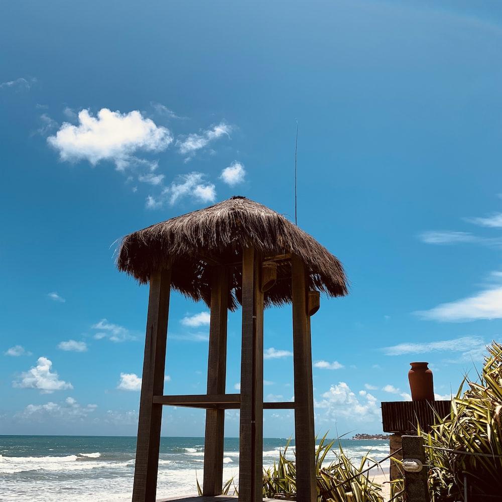brown wooden beach house near sea under blue sky during daytime